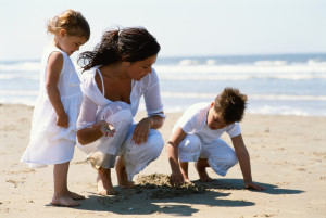 Mother and children searching for shells on the beach