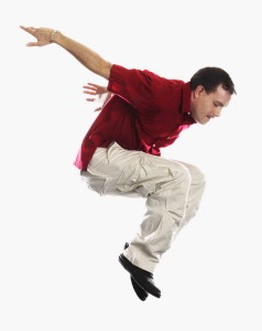 Young Man in Casual Attire Jumping Expressively into Air