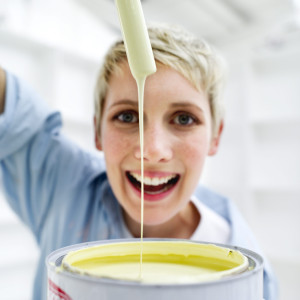 Young Woman Holding a Paint Brush Dipped in a Paint Bucket