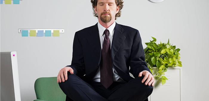 Businessman meditating on desk